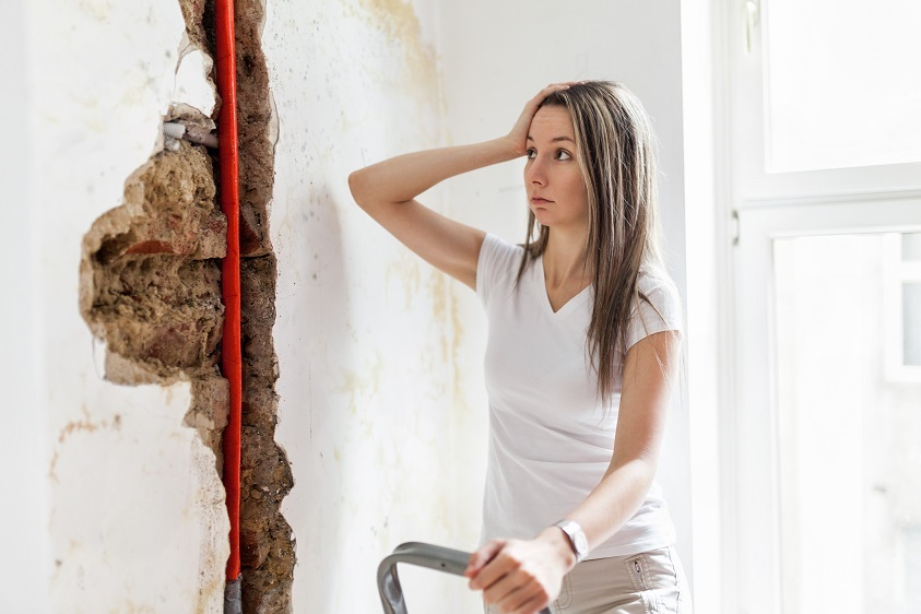 female student looking at damage after a water pipe leak at student accommodation