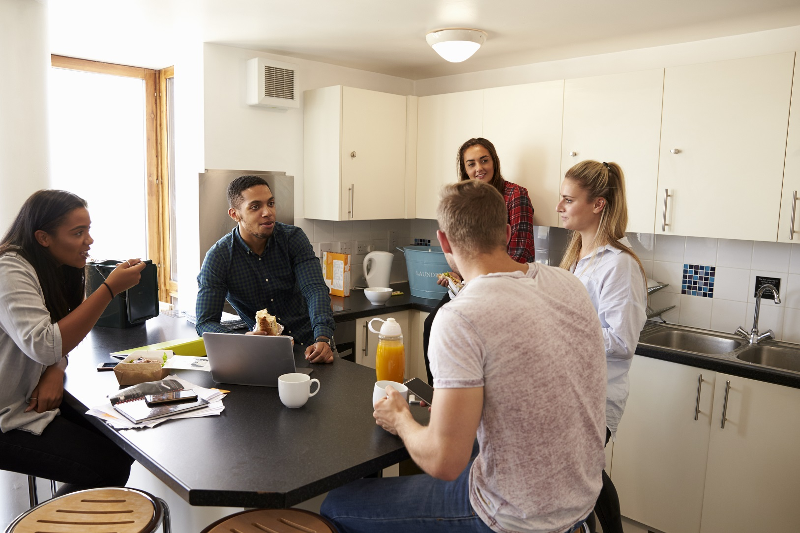 Students Relaxing In Kitchen Of Shared Accommodation in Coventry
